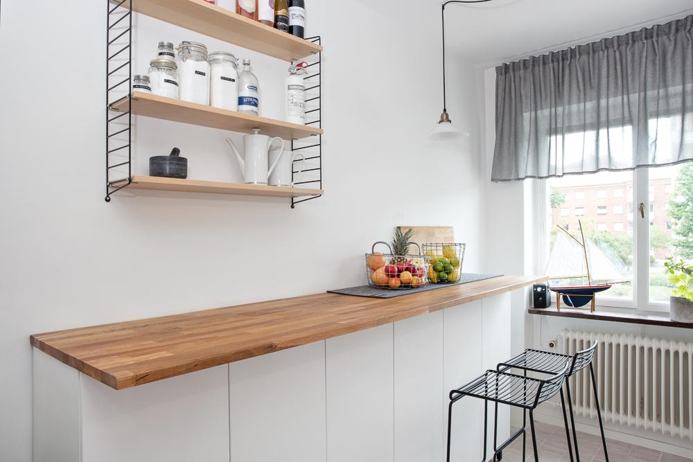 Andra sidan av köket med goda arbetsytor samt sittmöjlighet vid barskivan.