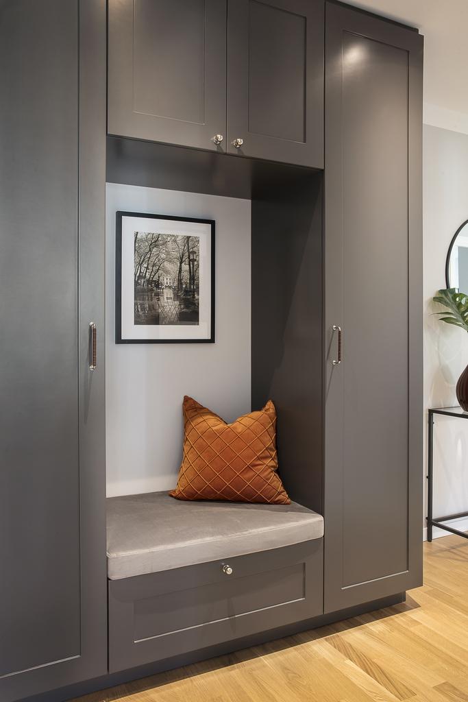 Platsbyggd garderobsmöbel med sittdel och läderinlindade handtag