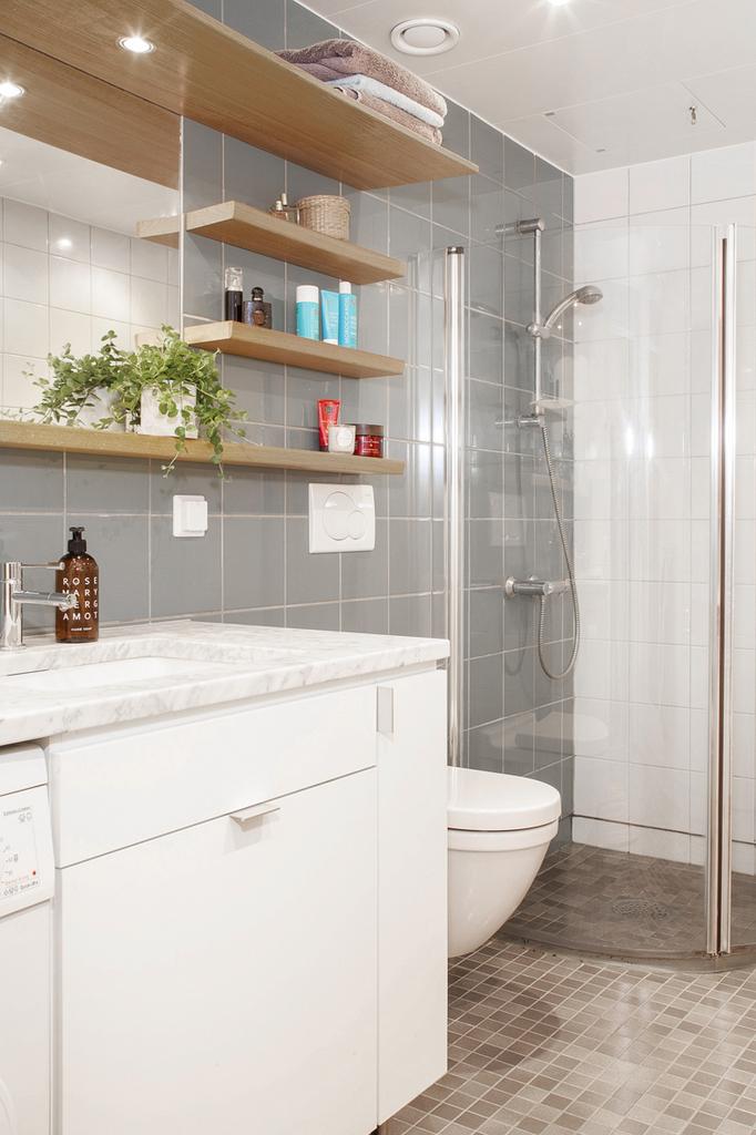 Det helkaklade badrummet har klinkers på golvet med golvvärme samt dusch bakom bakom vikväggar av glas