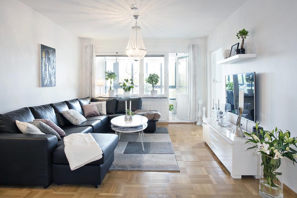 Stort vardagsrum med ljusa släta väggar och lamellparkett på golvet