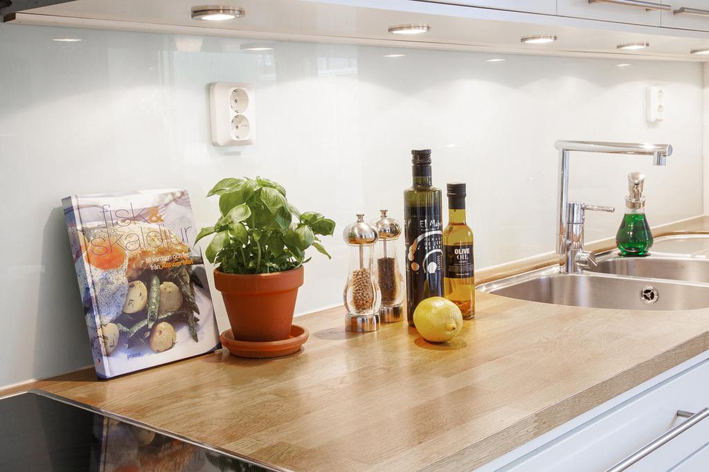 Den vita köksinredningen från Myresjö, matchar väl till den massiva hårdvaxade arbetsbänken av ek och stänkskyddet av glas