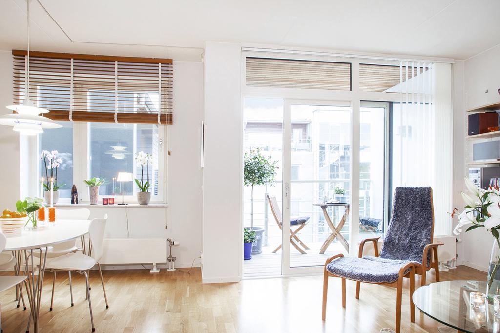 Kök, matplats och vardagsrum i öppen planlösning med fönster som vetter in mot gården