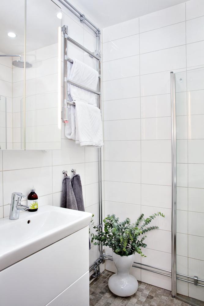 Renoverat badrum med vitt kakel och gråmelerad klinkers