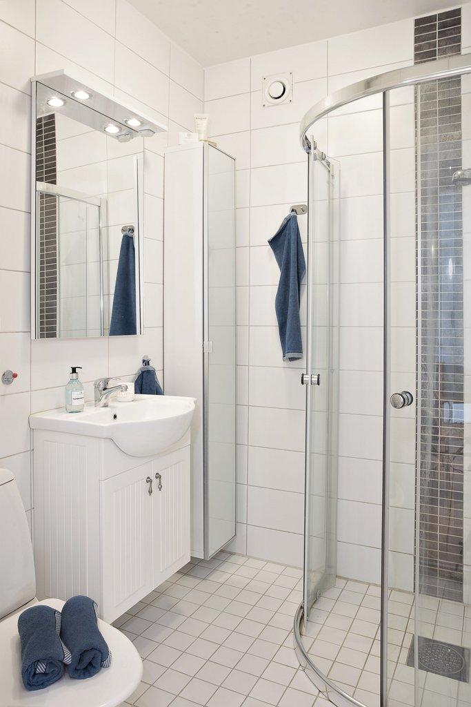 Badrummet är helkaklat med skjutbara duschdörrar och skåp för förvaring