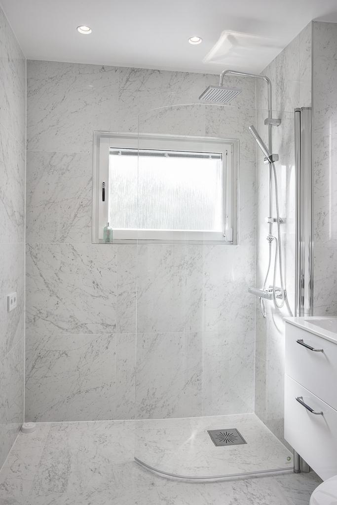 Totalrenoverat badrum med keramiska marmorplattor på både väggar och golv