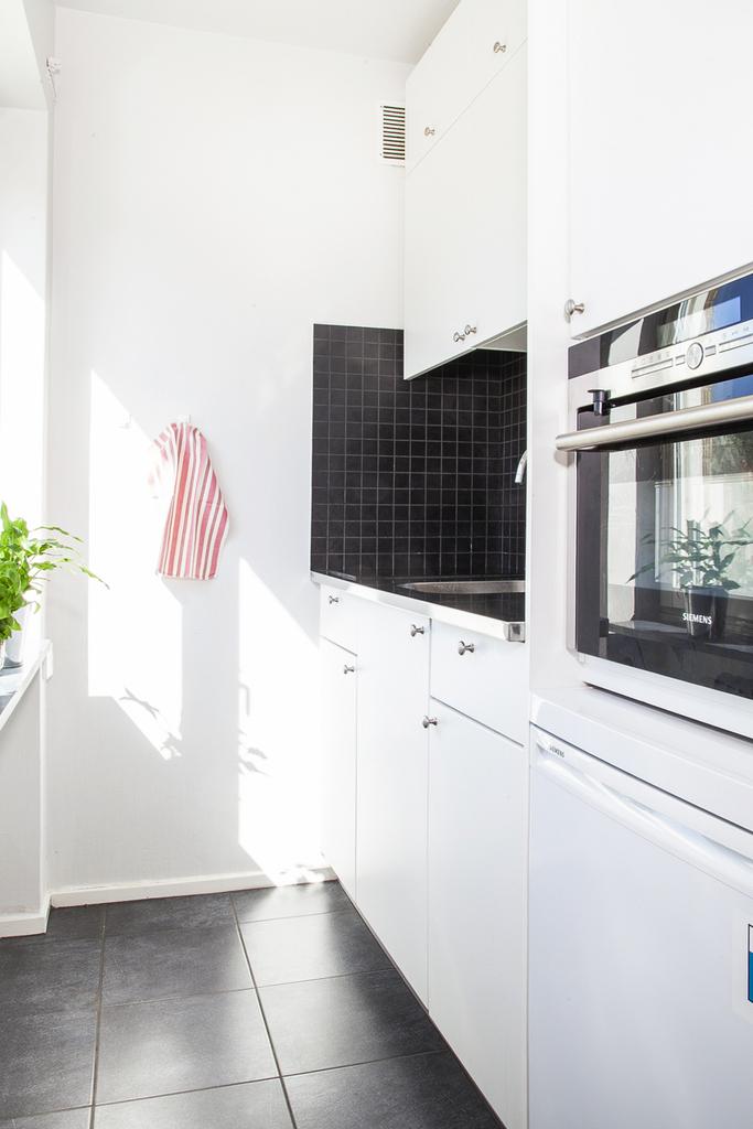 Stilrent kök med släta vita luckor