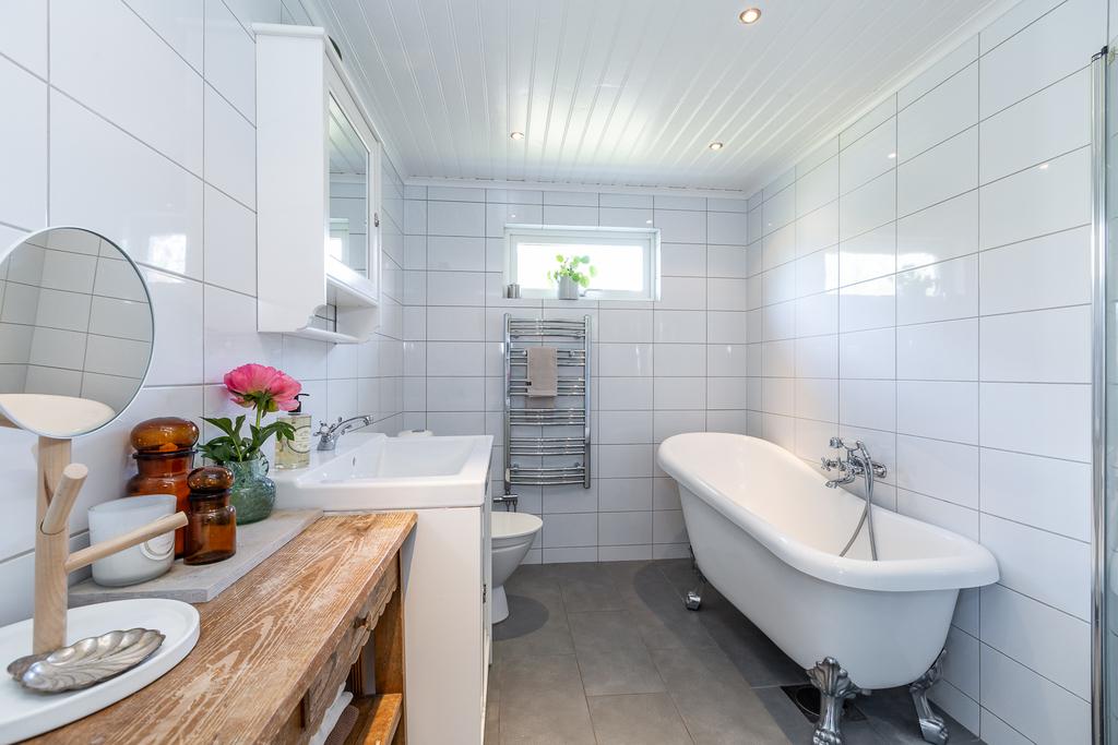 Helkaklat badrum med badkar och golvvärme via elslingor.