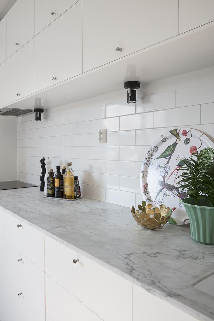 Köket har vitt kakel och bänkskiva i marmor