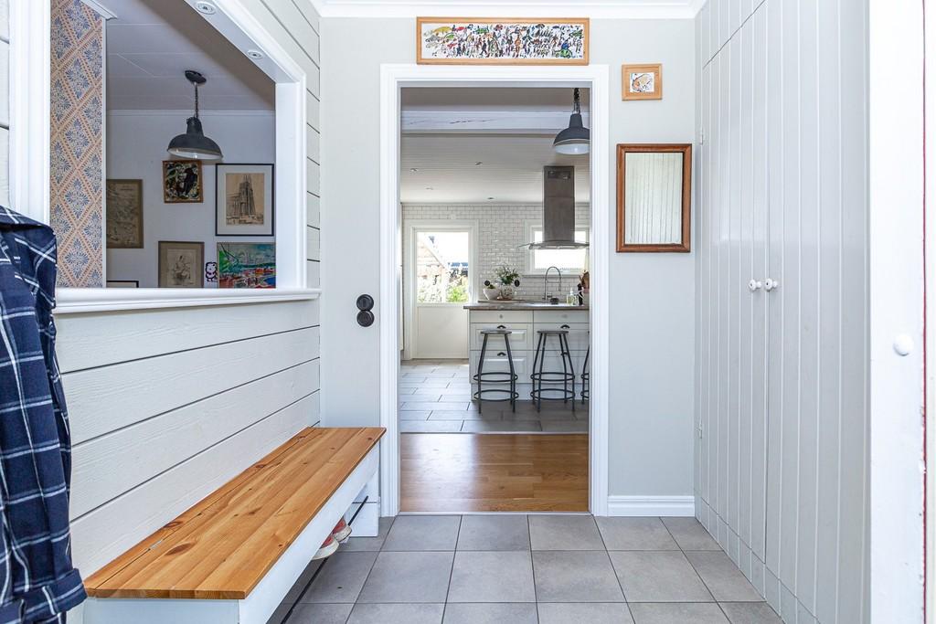 Hall med praktisk bänk och platsbyggd förvaring.