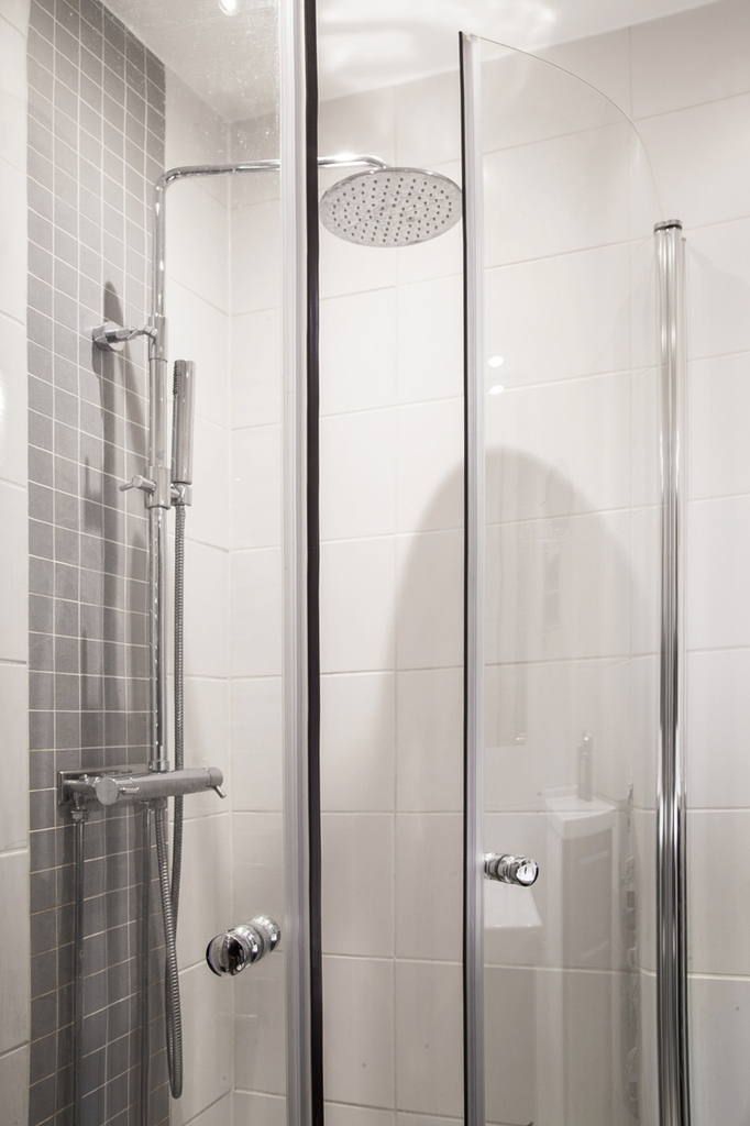 Bakom vikväggar av glas finns en duschhörna med både hand- och takdusch