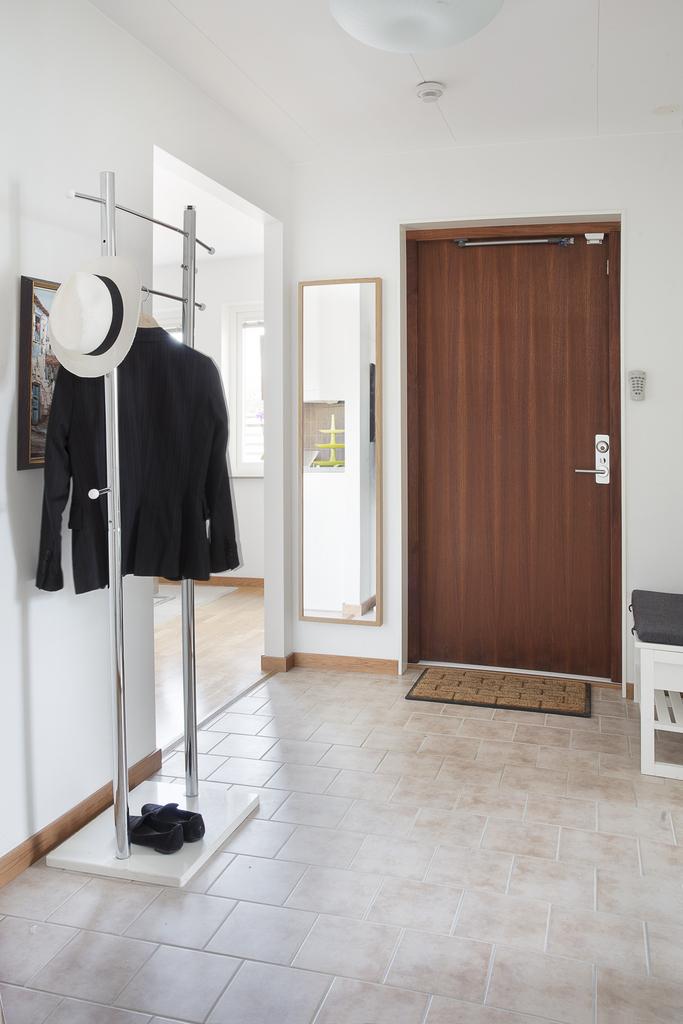 Entré med ljusa väggar och klinkers på golvet samt plats för avhängning