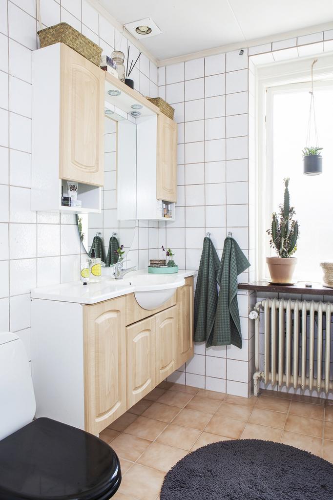Åter in i huset - Badrum 1 är helkaklat med kommod och skåp för förvaring