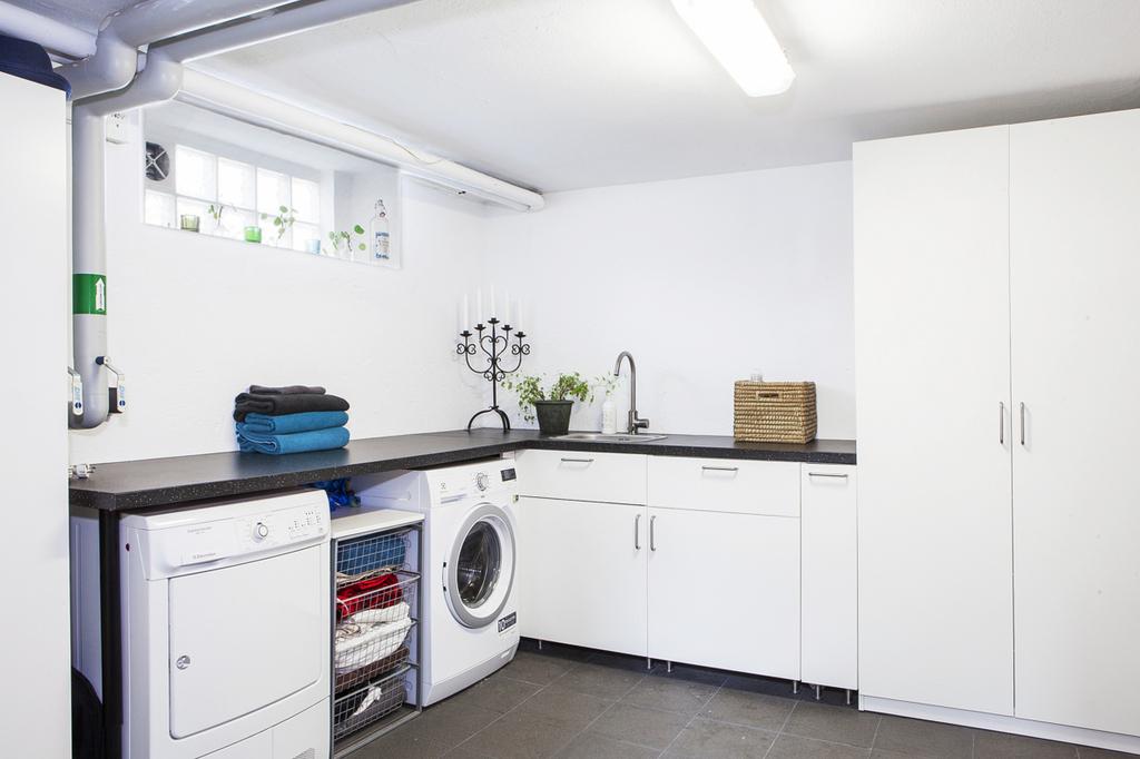 I källaren finner vi en rymlig tvättstuga med klinkergolv