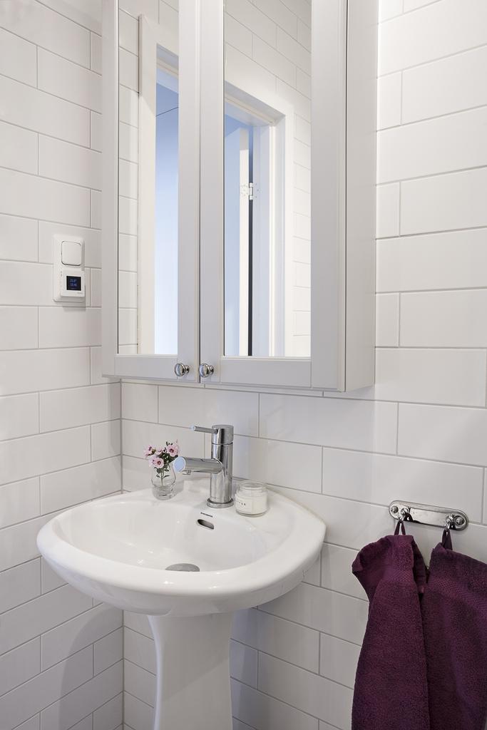 Här finns badrumsskåp och vitt kakel