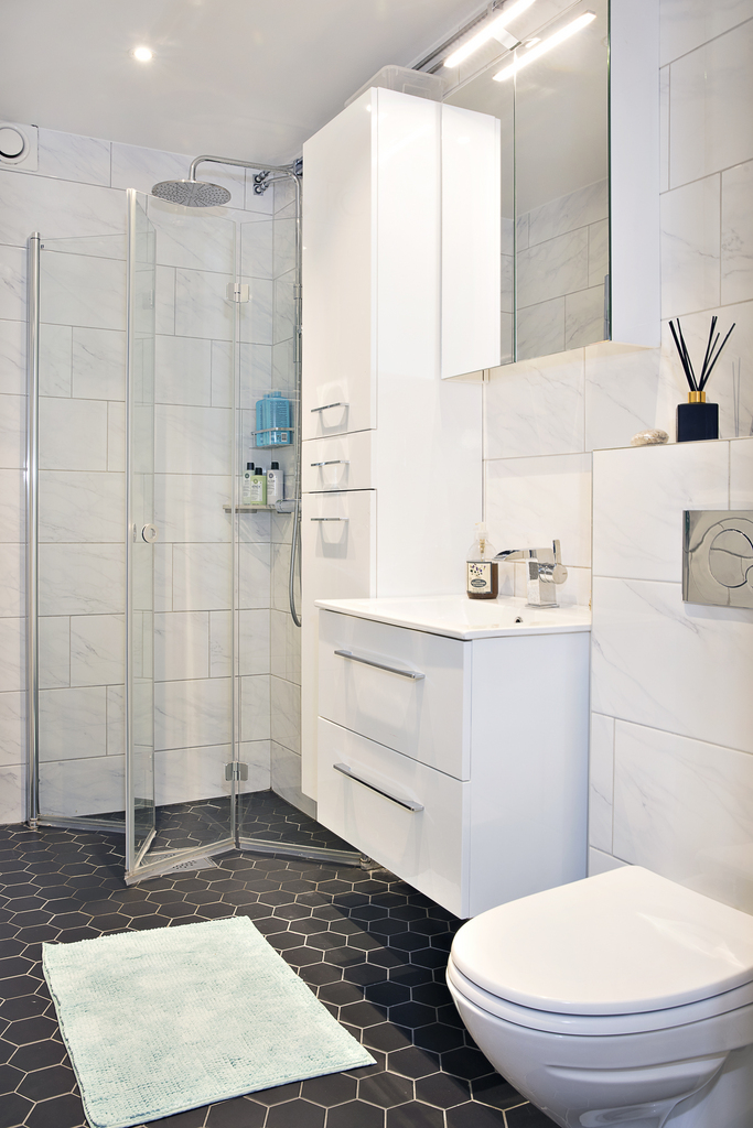 Det helkaklade badrummet har gott om plats för förvaring i både högskåp, badrumsskåp och kommod