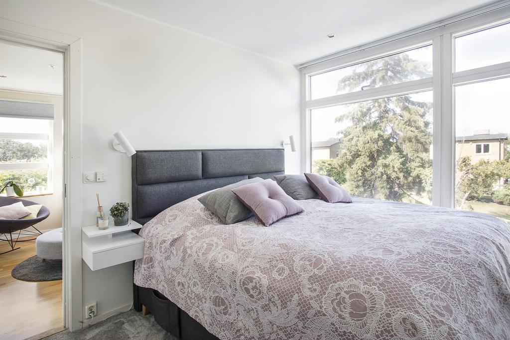 Sovrum 1 har släta ljusa väggar, fönster från golv till tak i norr samt grå heltäckningsmatta på golvet