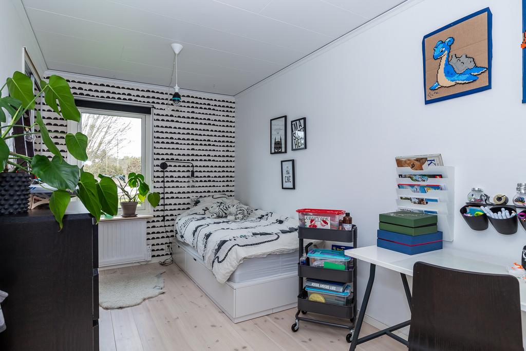 Sovrum 1 med trägolv och förvaring bakom skjutdörrar